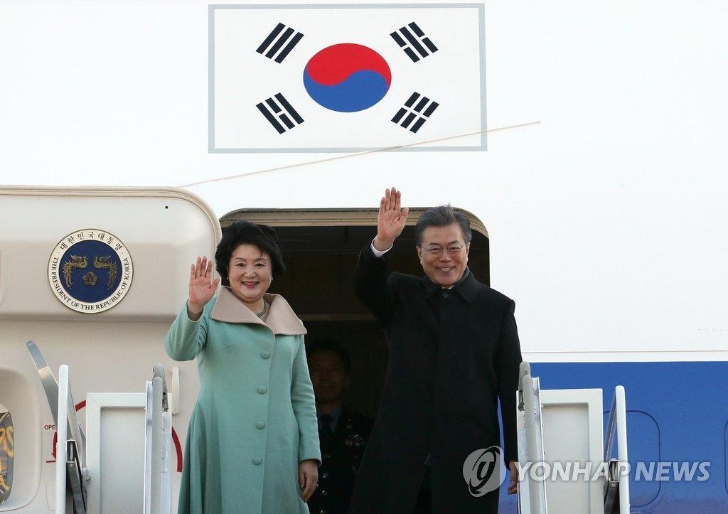 12月13日上午,在首尔机场,韩国总统文在寅(右)和夫人金正淑女士启程赴华时向群众挥手致意。(韩联社)
