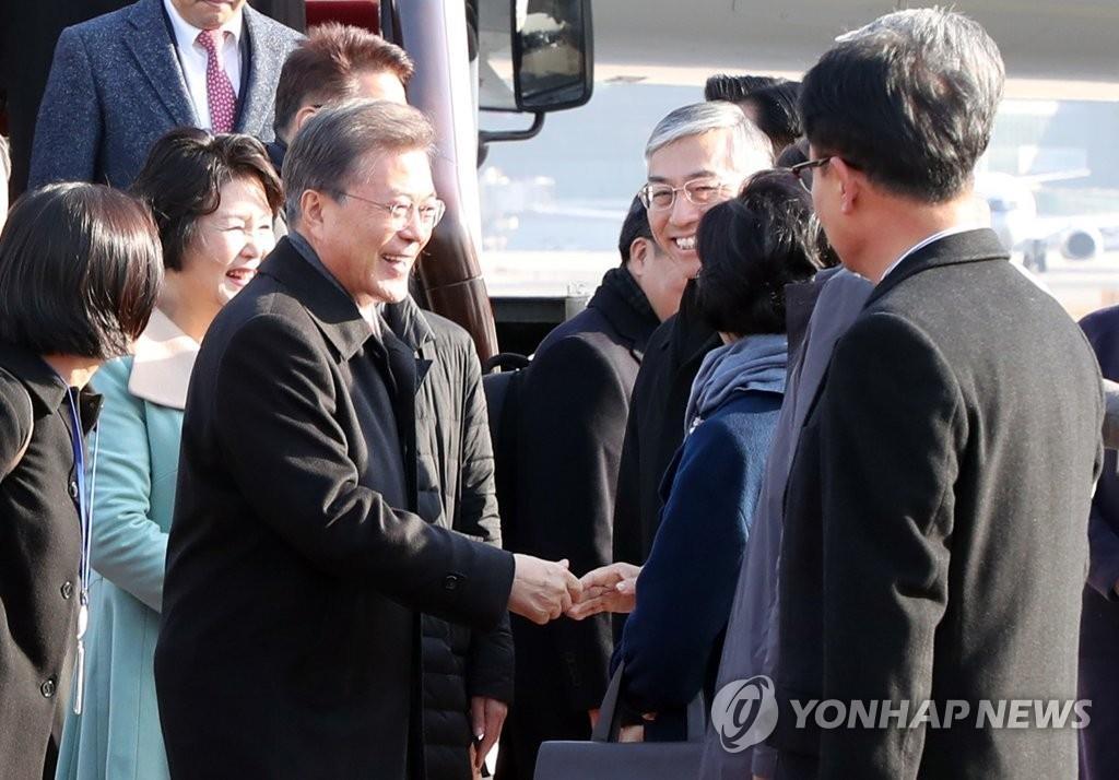 文在寅抵达首都机场后,同前来接机的人士握手问候。(韩联社)