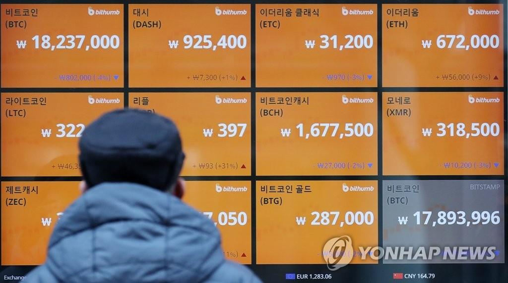 资料图片:12月13日下午,在首尔中区一家虚拟货币交易所,一位市民在查看虚拟货币行情。(韩联社)