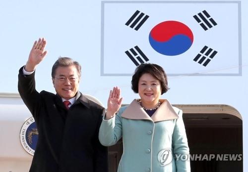 12月13日上午,在中国北京首都机场,韩国总统文在寅夫妇抵达后向众人挥手致意。(韩联社)