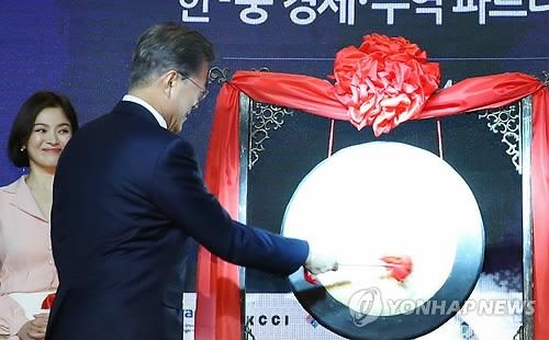 12月14日上午,在北京,文在寅为韩中经贸合作交流会敲锣开幕。(韩联社)