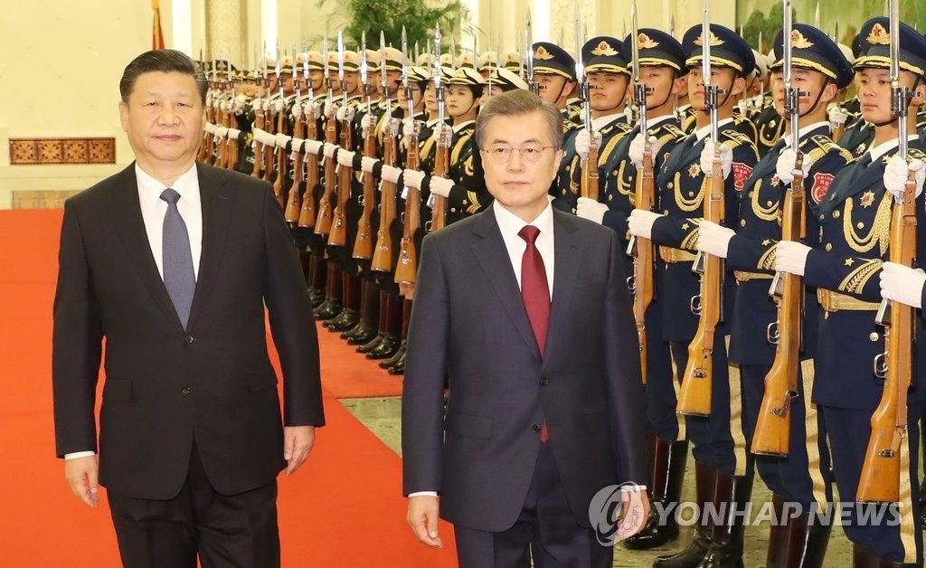 12月14日下午,在北京人民大会堂举行的欢迎仪式上,文在寅(右)和习近平检阅仪仗队。(韩联社)