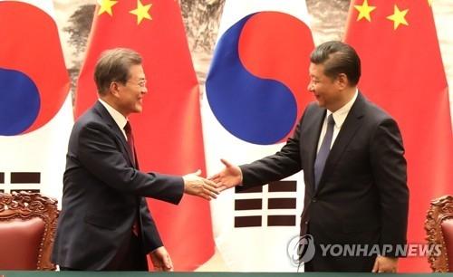 12月14日下午,在北京人民大会堂,韩国总统文在寅(左)和中国国家主席习近平握手。(韩联社)