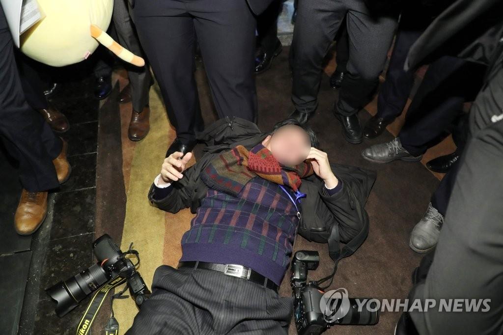 12月14日上午,在北京国家会议中心,一名随行采访总统文在寅访华活动的韩国摄影记者遭中方警卫殴打躺倒在地。(韩联社)