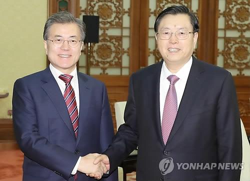 12月15日下午,在北京人民大会堂,韩国总统文在寅(左)同中国全国人大常委会委员长张德江举行会谈前握手合影。(韩联社)