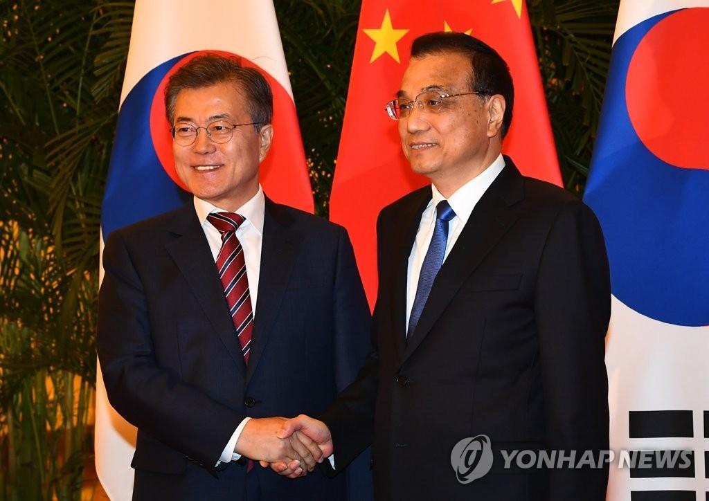 12月15日,在中国北京人民大会堂,韩国总统文在寅(左)会见中国国务院总理李克强,双方在会谈前亲切握手。 (韩联社)