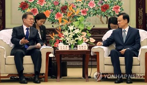 12月16日,在重庆渝州宾馆,韩国总统文在寅(左一)会见重庆市委书记陈敏尔(右一)。(韩联社)