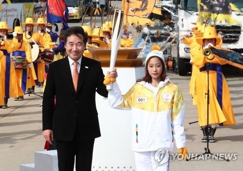 11月1日,在仁川大桥,花滑新星柳英从韩国总理李洛渊手中接过平昌冬奥火炬。(韩联社)