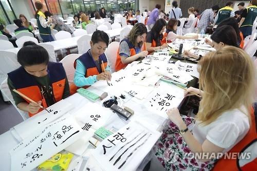 """资料图片:去年9月,在首尔,参加""""世宗学堂优秀学习者培训""""的外国人体验书法。(韩联社)"""