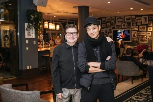 演员姜栋元(右)和导演西蒙·韦斯特(韩联社/YG娱乐提供)