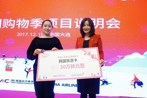 12月15日,2018年韩国购物季项目说明会在中国大连举行,韩国旅游卡中奖者(左)与韩国访问委员会相关负责人合影留念。(韩联社/韩国访问委员会提供)