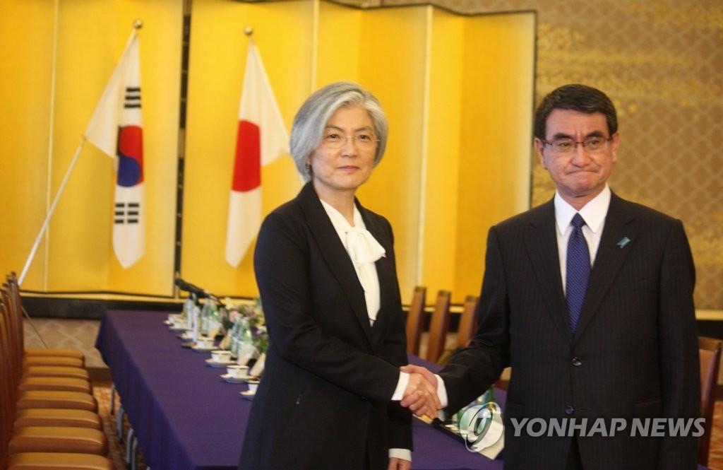 12月19日,在东京,韩国外交部长官康京和(左)同日本外相河野太郞举行会谈前握手。(韩联社)