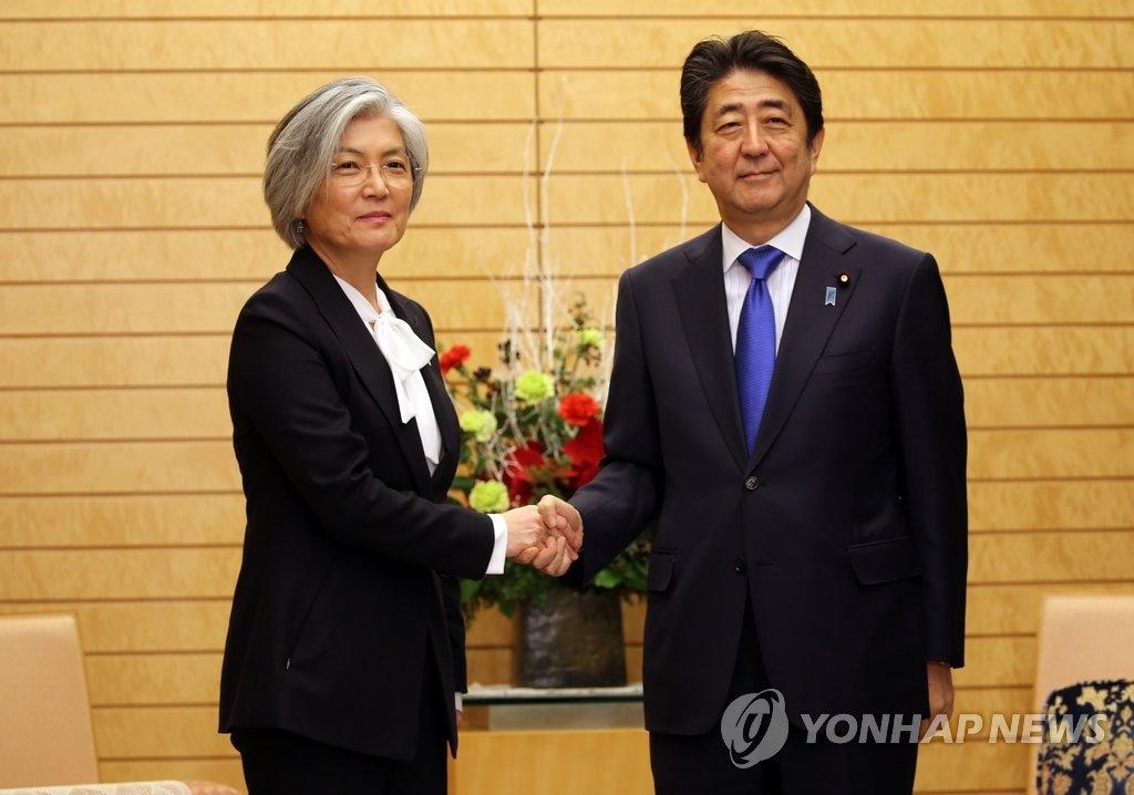 资料图片:12月19日下午,在东京,韩国外交部长官康京和(左)与日本首相安倍晋三握手合影。(韩联社)