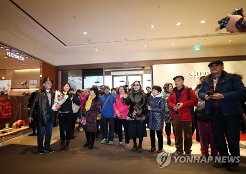 资料图片:12月5日下午,在首尔新罗免税店,中国政府开放部分赴韩团体游后首批中国游客在欢迎下进入免税店。(韩联社)