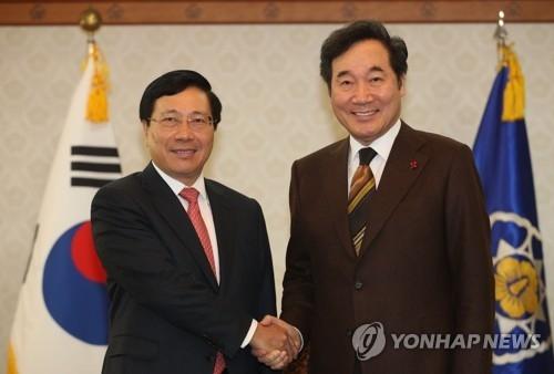 12月21日上午,在中央政府首尔办公楼,韩国总理李洛渊(右)同越南副总理范平明握手合影。(韩联社)
