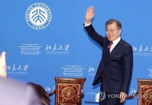 """资料图片:12月15日上午,在北京大学,韩国总统文在寅发表题为""""韩中青年紧握手,共创繁荣明天""""的演讲,向人群挥手致意。(韩联社)"""