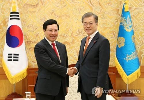 资料图片:12月21日下午,在韩国总统府青瓦台,韩国总统文在寅(右)同越南副总理兼外长范平明握手合影。(韩联社/青瓦台提供)