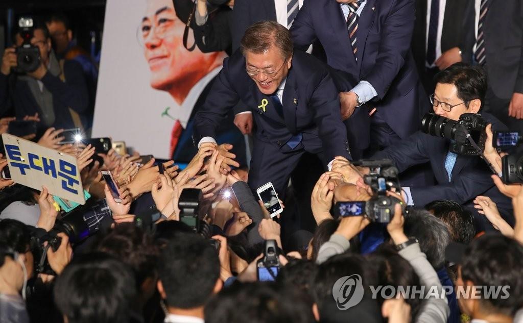 资料图片:文在寅当选总统后,与选民握手。(韩联社)