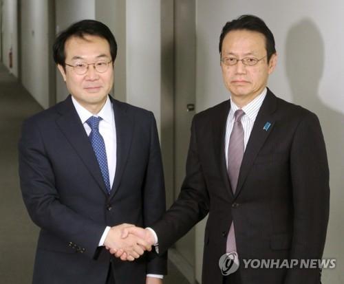 12月22日,在日本东京,朝核问题六方会谈韩方团长、外交部韩半岛和平交涉本部长李度勋(左)与日方团长、日本外务省亚洲大洋洲局局长金杉宪治握手合影。(韩联社)