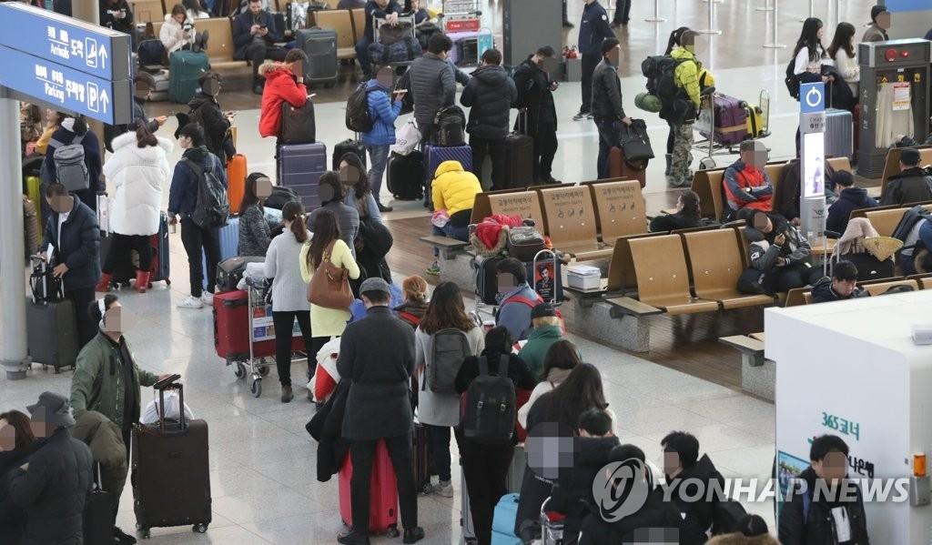 12月16日,在仁川机场,旅客排长队等候登机。(韩联社)