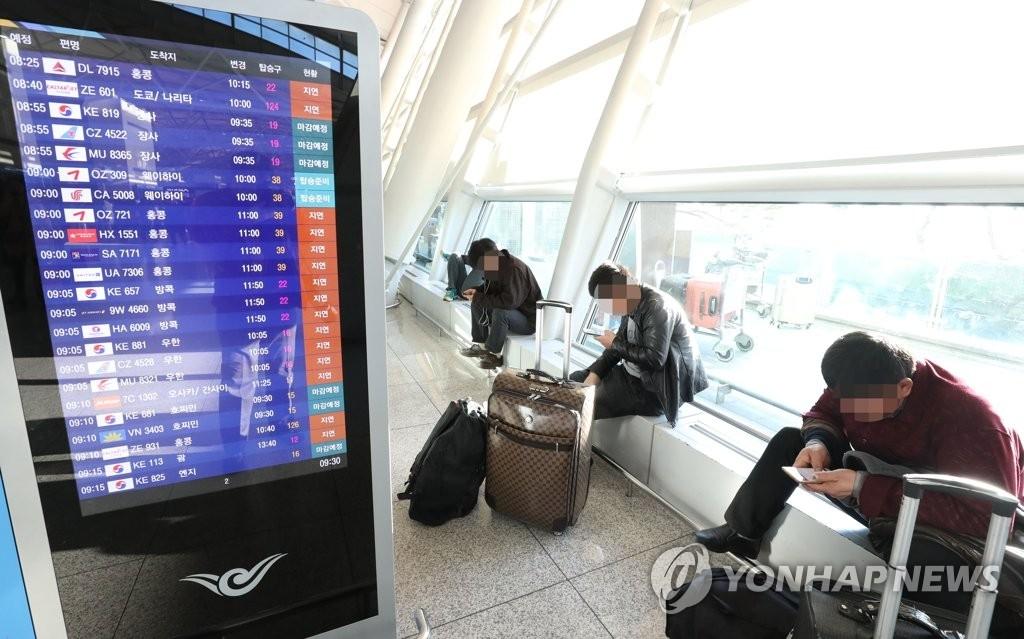 12月25日,在仁川机场,旅客等待办理登机手续。(韩联社)