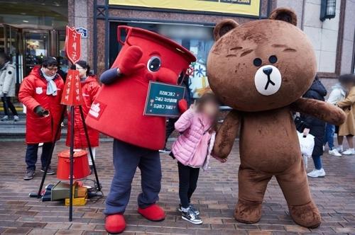 """12月25日,人气歌手兼演员金在中(右)迎圣诞节在大邱参与韩国""""慈善锅""""活动,化身LINE Friends布朗熊在街头和捐款市民进行免费拥抱(Free hug)。(韩联社/经纪公司C-jeS娱乐提供)"""