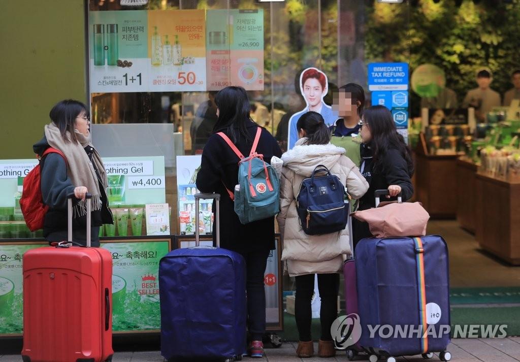 资料图片:2017年3月6日,在首尔明洞,中国游客光顾一家化妆品店。(韩联社)