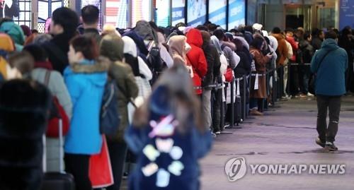 资料图片:12月5日一大早,在首尔市区某免税店门口,中国顾客冒着严寒排起长龙。(韩联社)