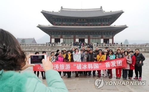 资料图片:在首尔景福宫,中国游客合影留念。(韩联社)
