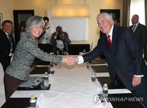 资料图片:韩国外交部长官康京和(左)同美国国务卿雷克斯·蒂勒森握手致意。(韩联社)