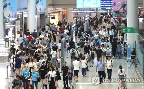 资料图片:仁川机场免税区的出境游客络绎不绝。(韩联社)