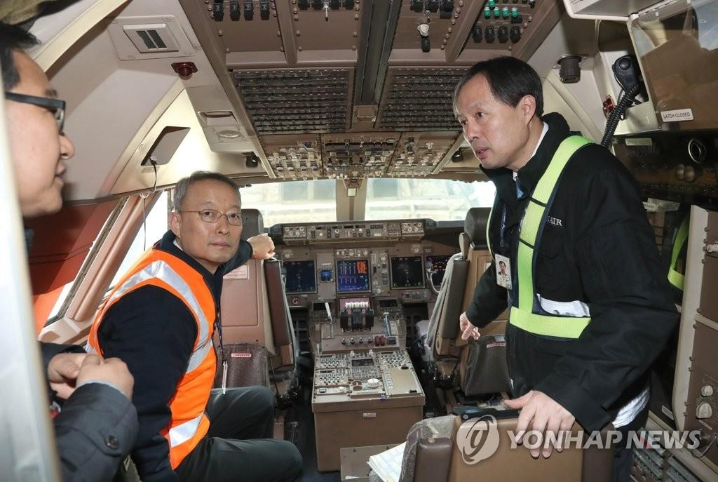1月1日,韩国产业通商资源部长官白云揆(左下)视察大韩航空位于仁川机场的出口货运站,图为白云揆在货机驾驶舱。(韩联社)