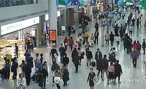 资料图片:仁川机场的游客络绎不绝。(韩联社)