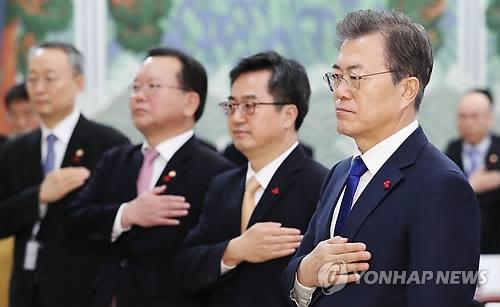 1月2日,在青瓦台,韩国总统文在寅(右一)在新年首场国务会议前向国旗敬礼。(韩联社)