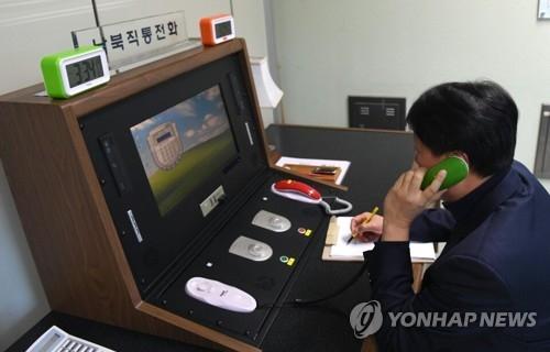 资料图片:1月3日下午3点34分,在板门店联合警备区联络事务所,韩方联络官拿起韩朝直通电话的话筒与朝方通话。(韩联社)