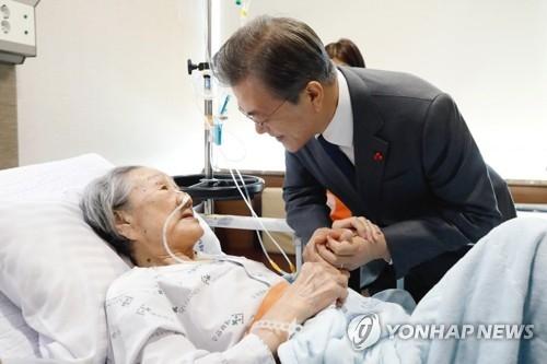 1月4日上午,在首尔延世大学医疗院,文在寅探望受害慰安妇金福童,祝这位年过九旬仍为女权奔走呼号的老人早日康复。(韩联社)
