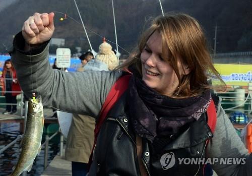 资料图片:外国游客在华川山鳟鱼庆典体验冰钓。(韩联社)