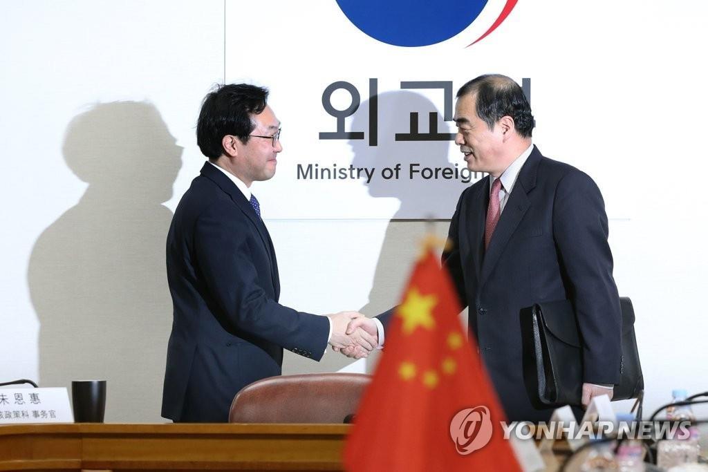 1月5日,在首尔外交部办公大楼,朝核六方会谈韩方团长李度勋(左)会见到访的中方团长孔铉佑,两人握手合影。(韩联社)