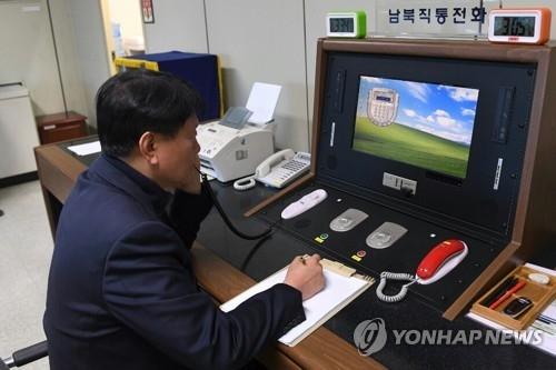 资料图片:韩方板门店联络官与朝方通话。(韩联社/韩国统一部提供)