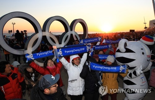 资料图片:1月1日,在江陵镜浦海边,平昌冬奥会志愿者们在宣传冬奥。(韩联社)