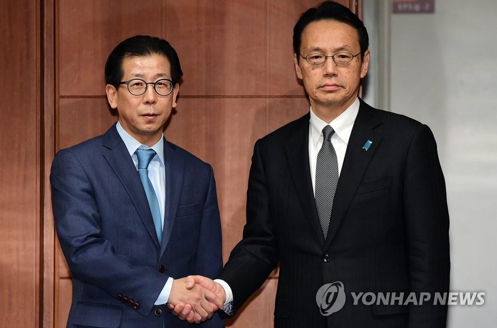 1月8日,在首尔韩国外交部大楼,韩国外交部东北亚局长金容吉(左)和日本外务省亚洲大洋洲局局长金杉宪治在会谈前握手合影。(韩联社)