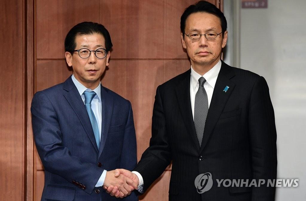 资料图片: 1月8日,在首尔韩国外交部大楼,韩国外交部东北亚局长金容吉(左)和日本外务省亚洲大洋洲局局长金杉宪治在会谈前握手合影。(韩联社)