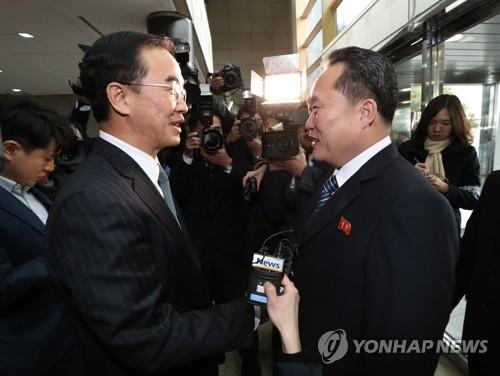 """1月9日,在韩朝边境的板门店""""和平之家"""",韩朝高级别会谈韩方团长赵明均(左)和朝方团长李善权握手致意。(韩联社)"""