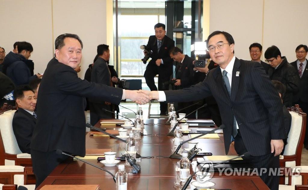 """1月9日,在板门店""""和平之家"""",统一部长官赵明均(右)和朝方代表李善权在会谈前握手。(韩联社/共同摄影采访组提供)"""