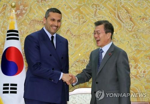 1月9日下午,在青瓦台,韩国总统文在寅(右)同来访的阿联酋王储特使卡尔杜恩·阿尔·穆巴拉克亲切握手。(韩联社)