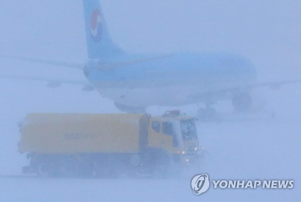 1月11日上午,在济州机场,除雪车正在进行除雪作业。(韩联社)