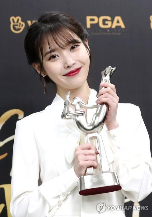 歌手IU手捧金唱片大赏奖杯。(韩联社)