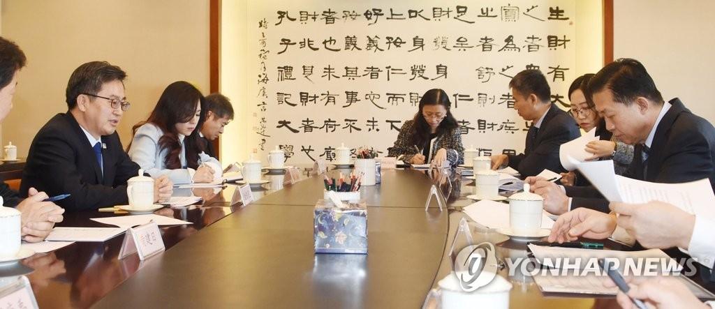 资料图片:12月15日,在中国北京,韩财长金东兖(左)同中国财政部长肖捷举行会谈。(韩联社/企划财政部提供)
