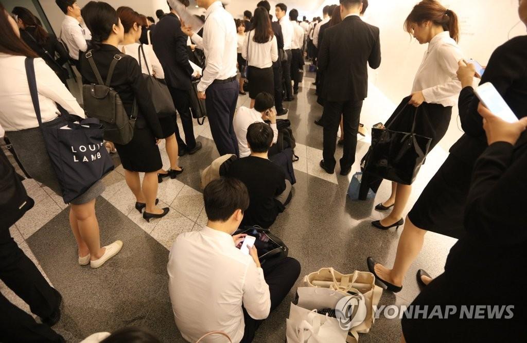 资料图片:2017年9月13日,在金融机关联合招聘博览会上,应聘者等待现场面试。(韩联社)