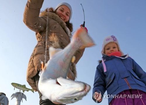 资料图片:1月14日,在韩国华川郡,游客冰钓鳟鱼。(韩联社)